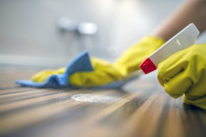 A person cleaning wood flooring with latex gloves
