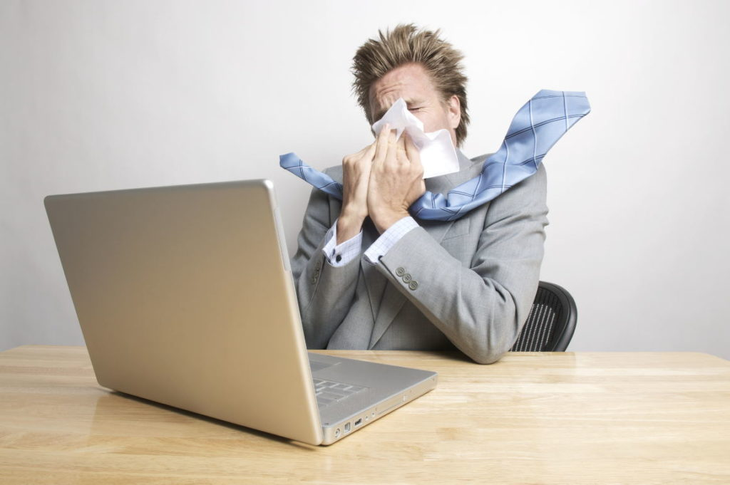 Sick man in front of a laptop computer blowing his nose with a tissue