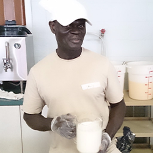 A black individual holding a pitcher of milk