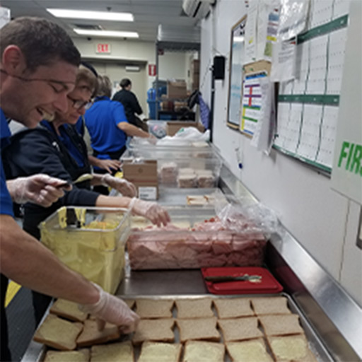 A PPC team member preparing sandwiches for the homeless